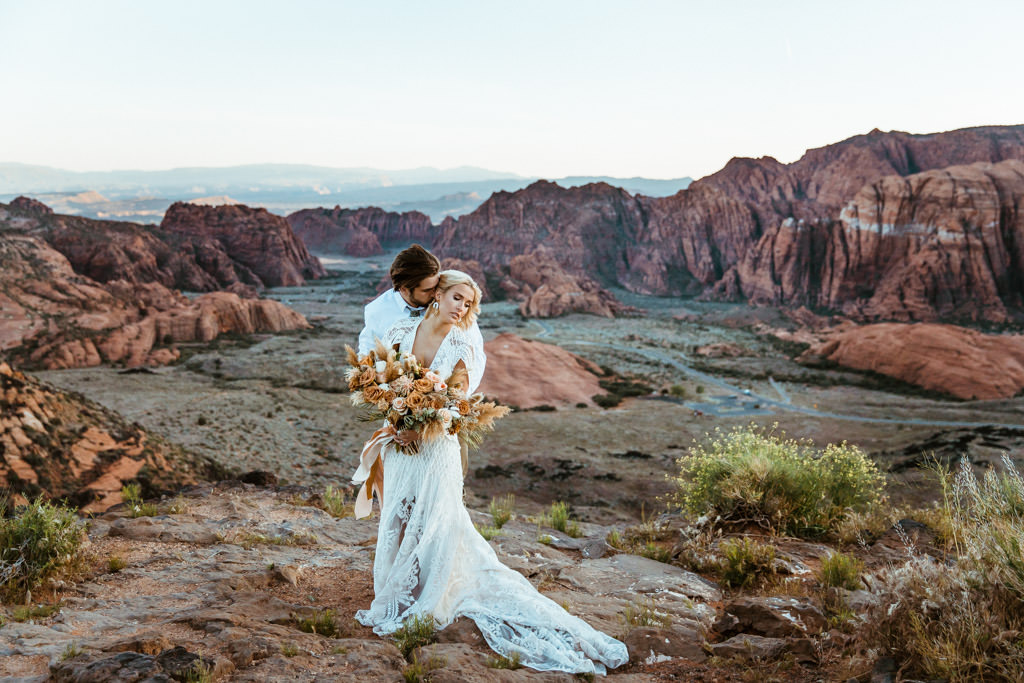 Surrounded by the red rock mountains of Zion National Park, a couple embraces during their boho elopement.