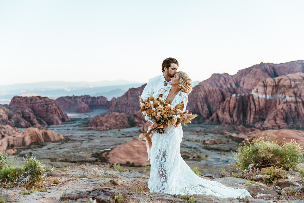 Couple shares a kiss after their boho elopement in Zion National Park.