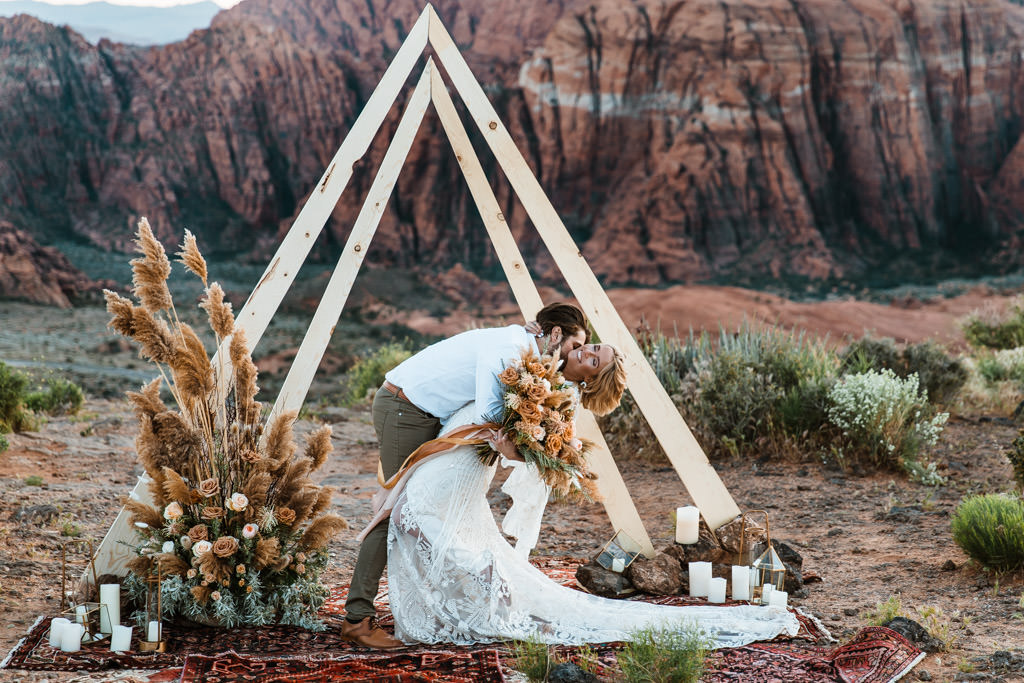Groom dips his bride for their first kiss after a small wedding ceremony in this boho Zion National Park elopement.