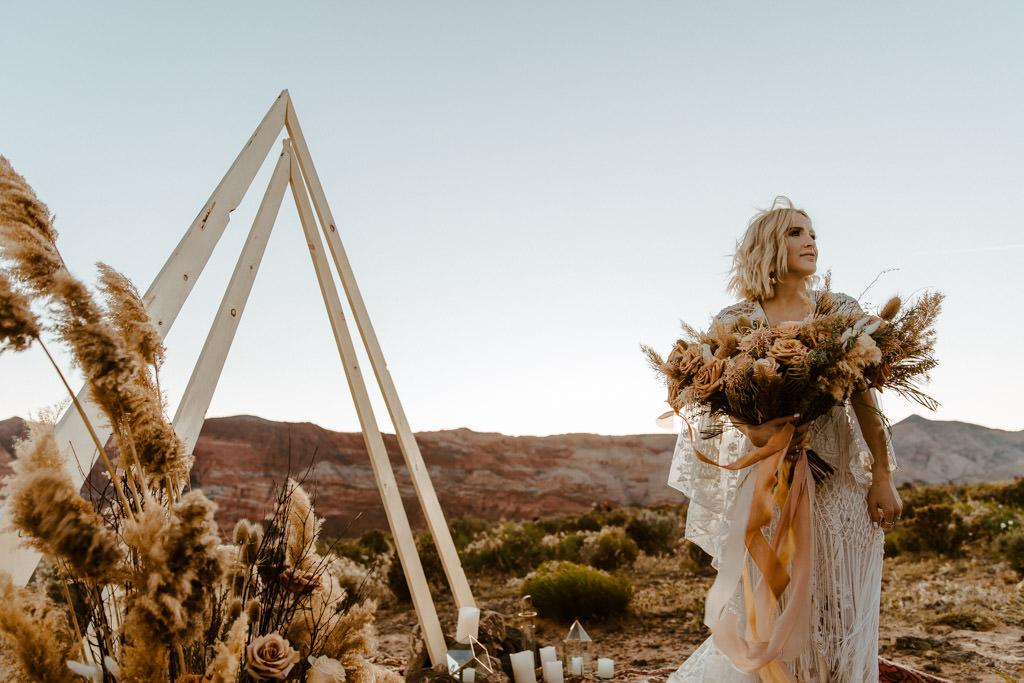 Bride holds her bouquet of dried florals for this earth-toned boho elopement.
