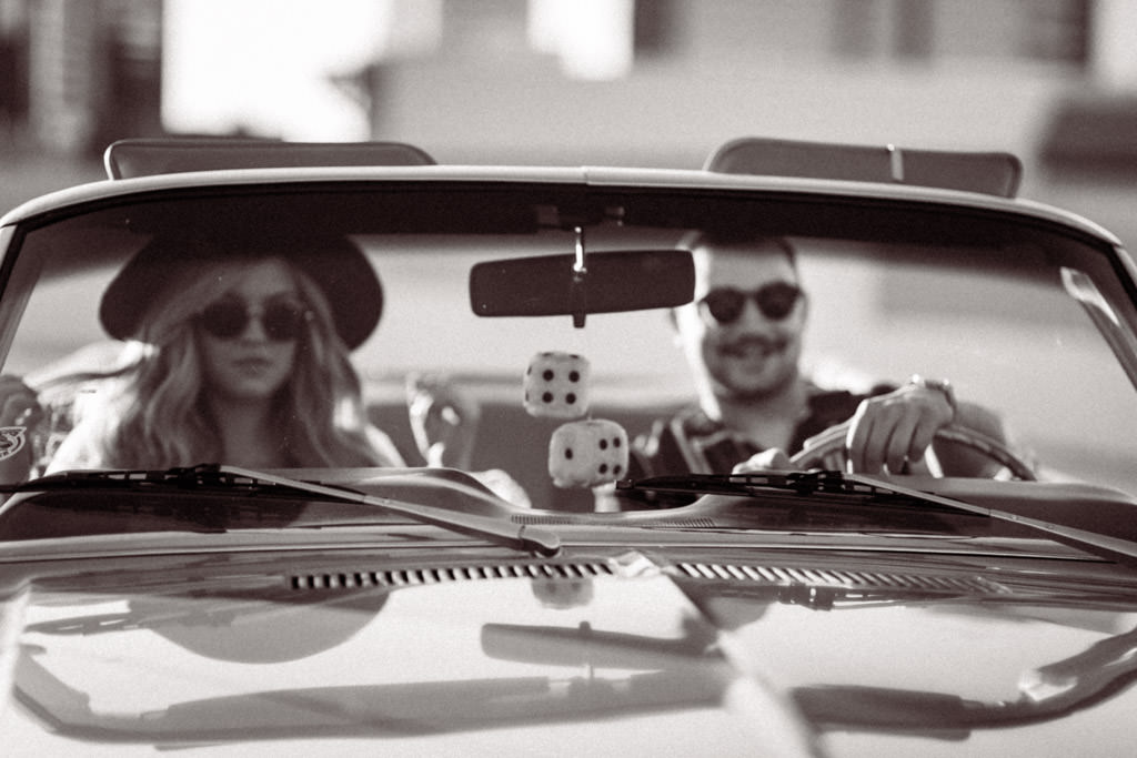 Couple looks out the front of their vintage 1968 Ford Mustang during their engagement photo session on a parking garage downtown LA rooftop.