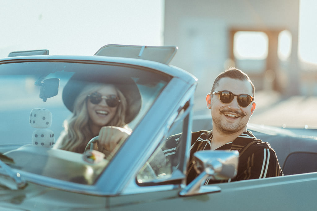 Couple smiles out of their convertible 1968 Ford Mustang during their vintage-inspired LA rooftop engagement session.
