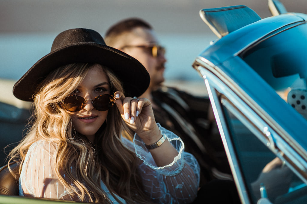 Woman tilts her sunglasses down to look into the camera during her engagement photo session on a parking garage LA rooftop in downtown Los Angeles.