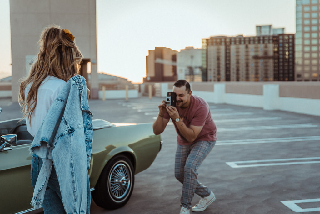 Soon-to-be groom captures his fiancee on a vintage camera during their LA rooftop engagement photo session.