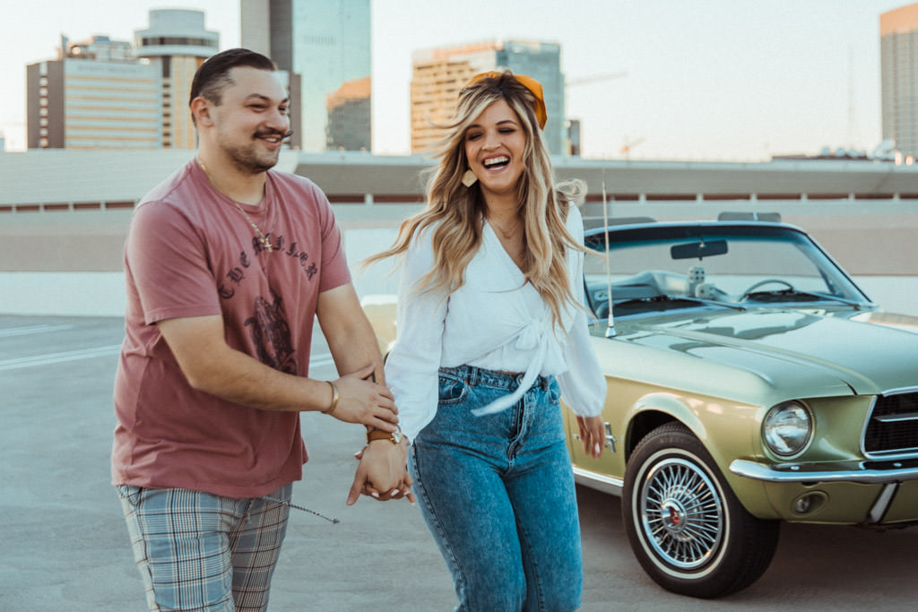 Couple runs across a downtown LA rooftop during their engagement photo session.