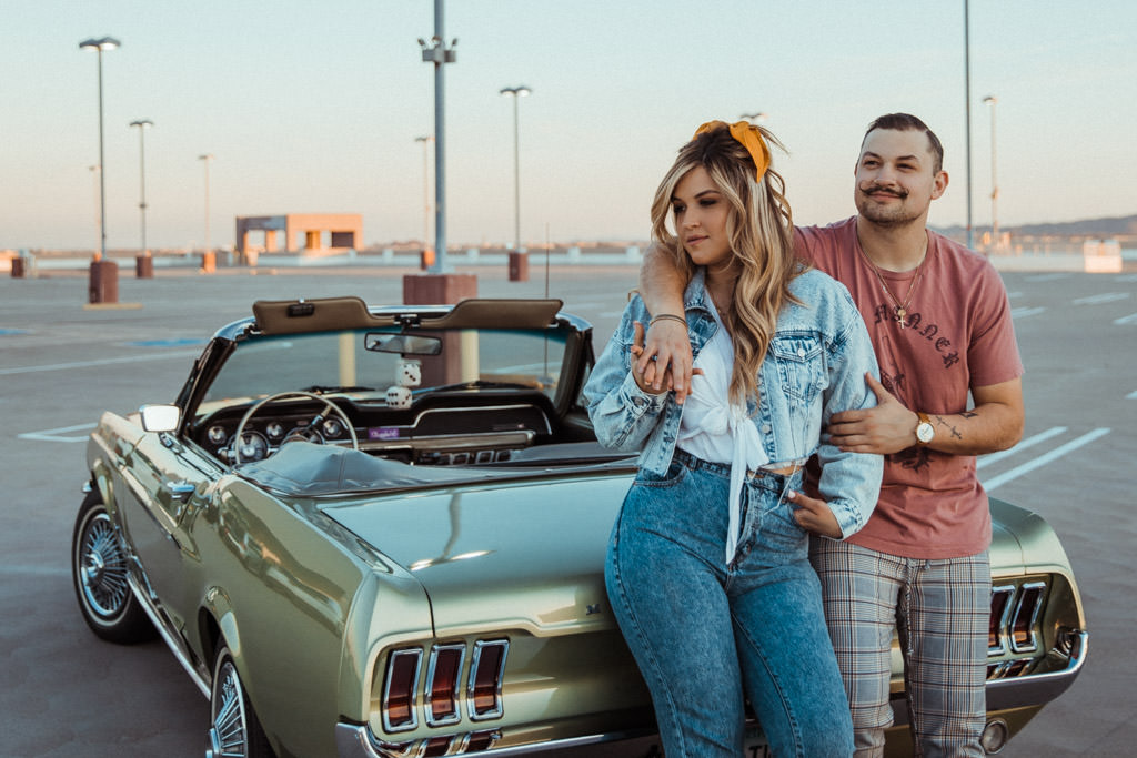 Couple leans on the back of their vintage 1968 Ford Mustang during their engagement photo session on a LA rooftop of a parking garage in Downtown.