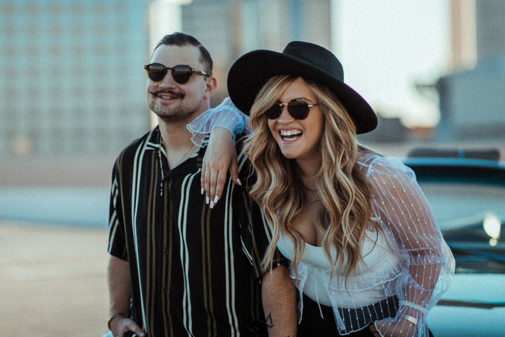 Couple laughs on a parking garage rooftop in downtown LA during their engagement photo session.