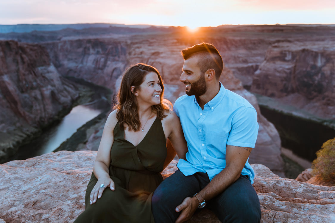 Couple enjoys an Arizona sunset over Horseshoe Bend during their hiking adventure engagement session.