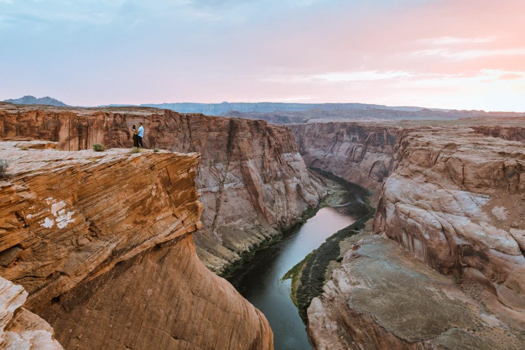 Couple overlooks the grand Horseshoe Bend during their engagement photo session in Page, Arizona with elopement photographer Wind and Sky Photography.