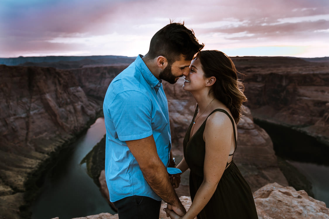 Engaged couple stand above Horseshoe Bend during their engagement photo session.