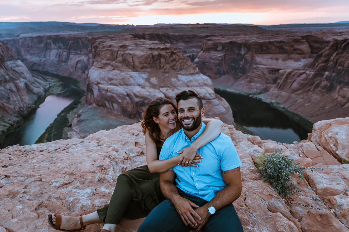 Couple smiles for a photo in front of Horseshoe Bend during their engagement session.