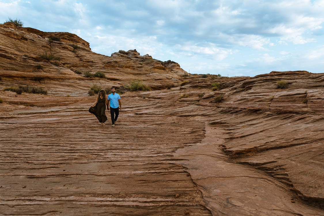 Couple explores red rock formations during their Horseshoe Bend engagement photo session.