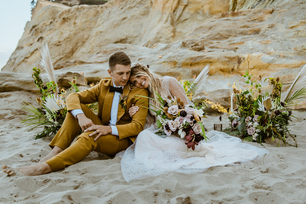 Couple sits on the soft sand in their wedding dress and suit after their Malibu beach elopement.