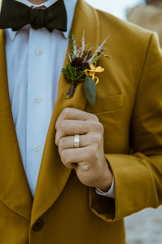 Groom shows off his wedding ring and boutonniere after an elopement on a Malibu beach in California.