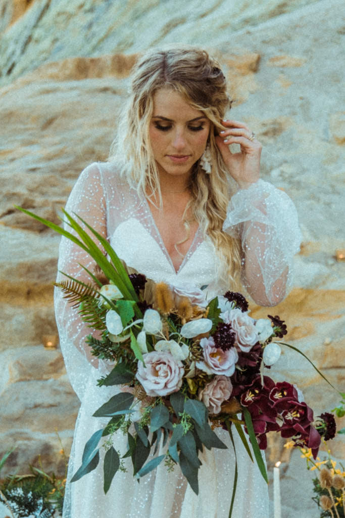 Bride shows off her bridal floral bouquet and wedding dress before an elopement on a Malibu, California beach.