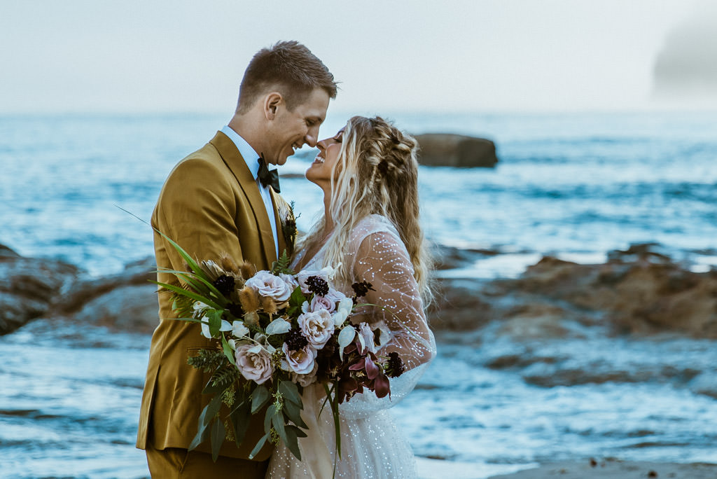 Bride and groom in front of the ocean during their Malibu beach elopement and small wedding.