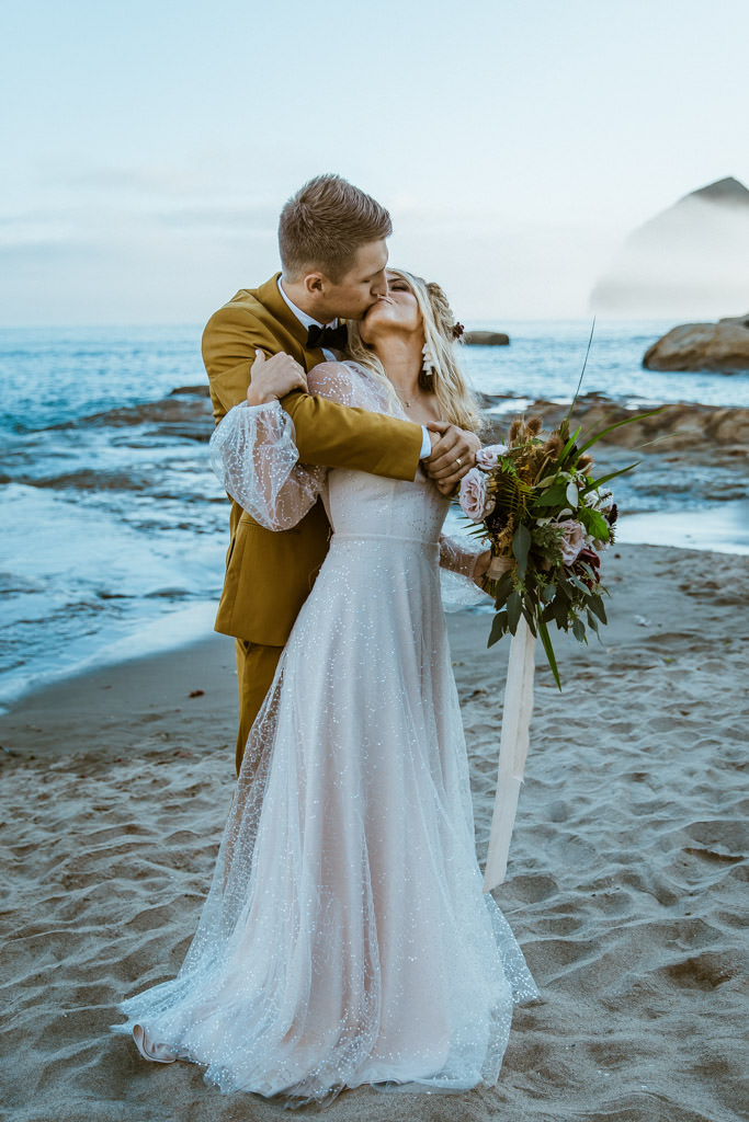 Couple kisses in front of the ocean during their elopement on a beach in Malibu, California.