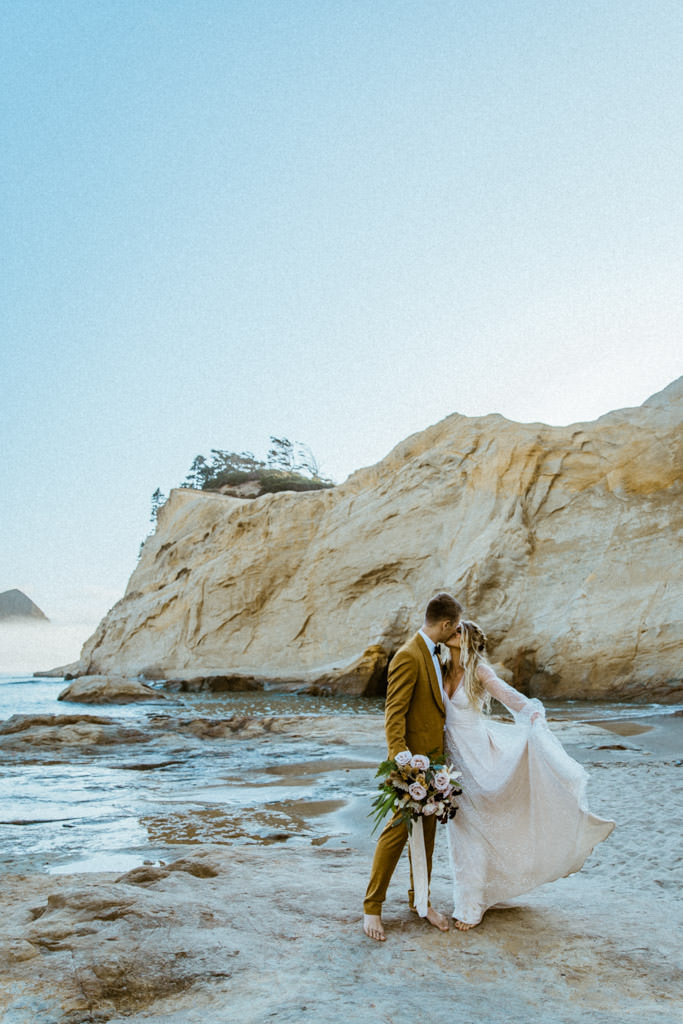 Bride holds her wedding gown above the sand during her Malibu beach elopement.