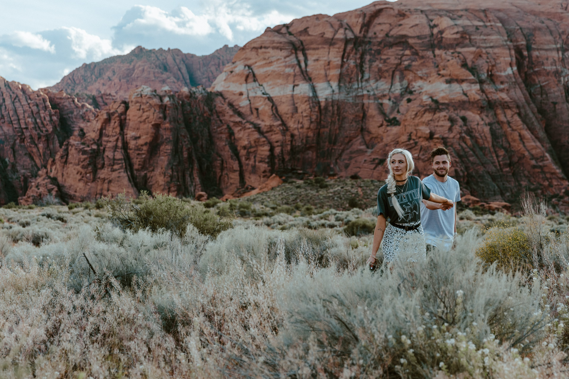 Couple holds hands while they explore Red Rock Canyon during their engagement session.