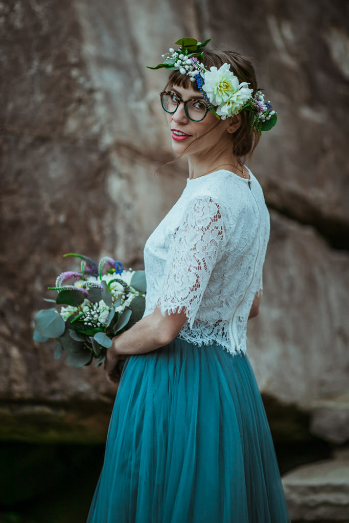 Bride in a blue wedding dress and floral crown before her spring mountain elopement.
