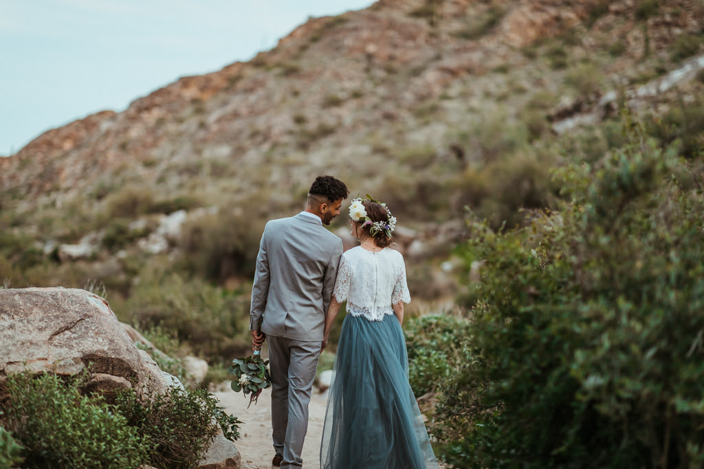 Bride and groom explore the mountain after their spring elopement.
