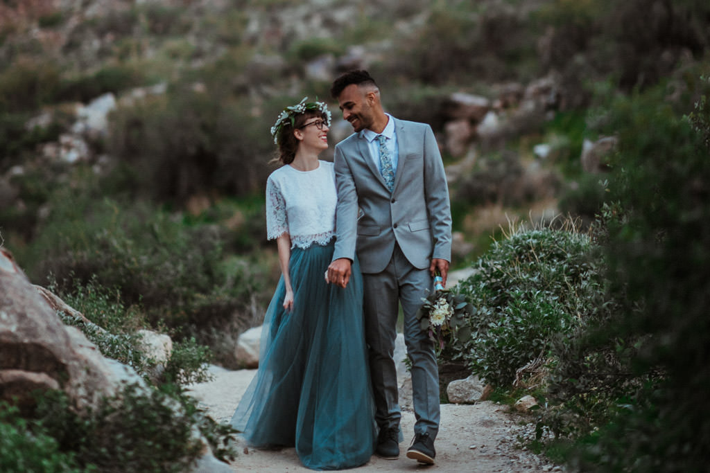 Couple smiles at each other as they walk a hiking trail in the White Tank Mountain Range during their spring elopement.
