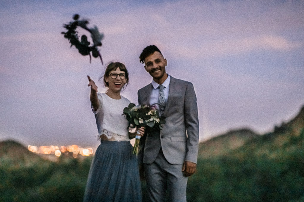 Bride tosses her flower crown at the end of her spring mountain elopement.