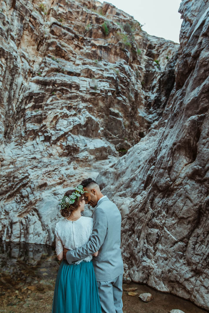 Small wedding photographer Wind and Sky Photography captures a bride and groom in front of a waterfall during their spring mountain elopement.