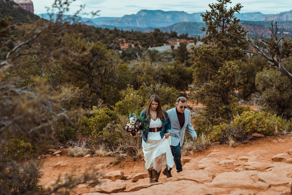 Bride's father escorts her up a hiking trail in Sedona, Arizona during her unique outdoor elopement.