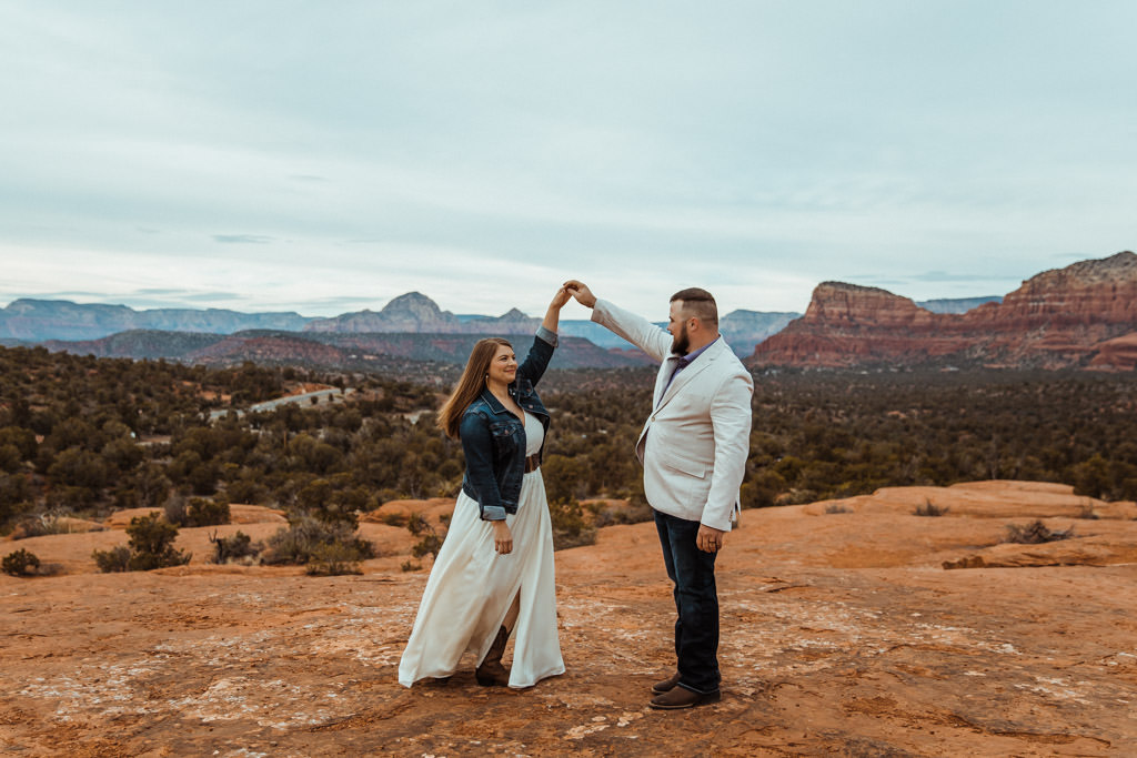 Newly married couple enjoys a first dance on the Bell Rock view point after their Sedona elopement wedding.