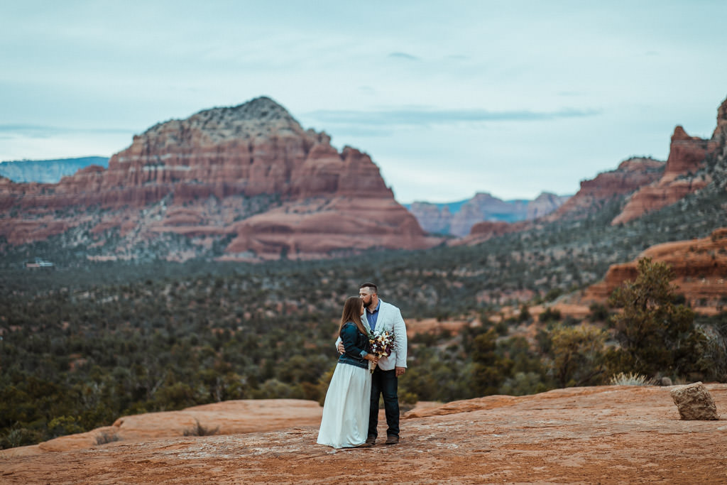 Lost in the panoramic views of Sedona, a couple takes a moment to steal a kiss after their elopement.