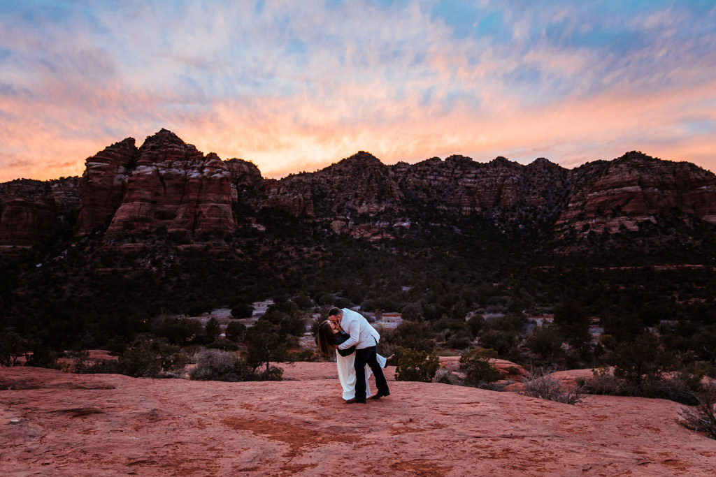 Groom dips his bride for a kiss after their elopement in front of this Sedona sunset.