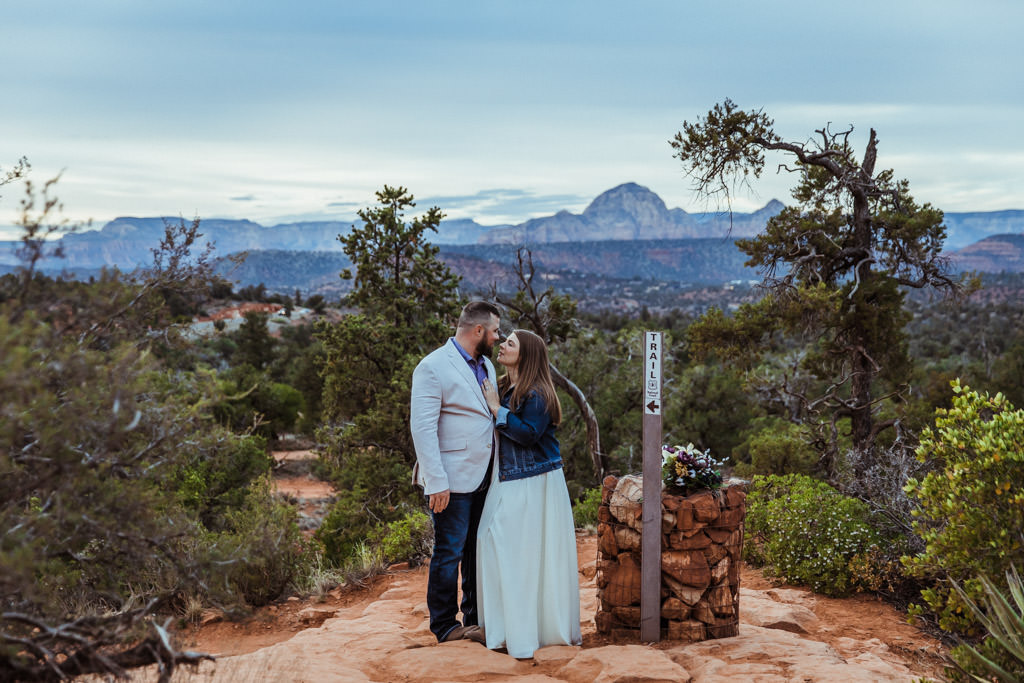 Couple hikes up a trail on Bell Rock in Sedona during their elopement.