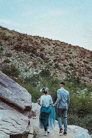 Newly married couple stays on a trail to minimize the environmental impact of their eco-friendly wedding in nature.